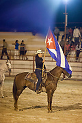 Female rider on a horse flying a Cuban flag to mark the opening of the Rodeo. Cuban locals attend a Rodeo in Ciego de Avila province, Cuba.