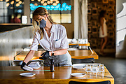 30248072A Nashville, Tenn., - Server Taylor Wagner, puts out clean napkins and silverware after sanitizing the table between patrons at Pinewood Social. Pinewood Social has taken steps to socially distance in their restaurant and take temperatures of every patron that walks through the door.