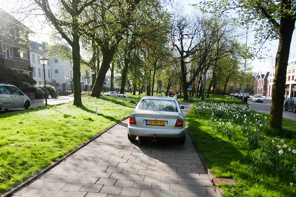 Een automobilist rijdt met zijn auto over een fietspad.<br /> <br /> A car is illegally riding on a bicycle path.
