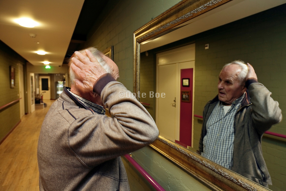 senior man looking at himself in the mirror and adjusting his hair