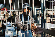 Javier Molina, left, shakes hands with Juan Pablo Gomez Gonzalez, a student, during a break at the Lady of Lebanon religious event just outside of Leamington. Molina, a migrant worker, is working today for the church as a short order cook. The fence separates the cooking area from the general public for safety reasons.