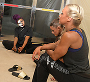3 Competitors consider what comes next. One in particular looks on in half and half-painted face.