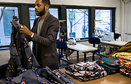 17 MARCH 2017 -- ST. LOUIS -- Fashion designer Reuben Reuel Riddick, of Demestik by Reuben Reuel, organizes an order of items purchased by Debbie Chase from his collection at the St. Louis Fashion Incubator in downtown St. Louis Friday, March 17, 2017. Riddick relocated his company from Brooklyn to St. Louis after being selected for the incubator's Inaugural Designer Class. Photo © copyright 2017 Sid Hastings.