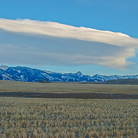 Lenticular clouds hover over the Bridger Mountains and harvested wheat fields north of Bozeman, Montana.