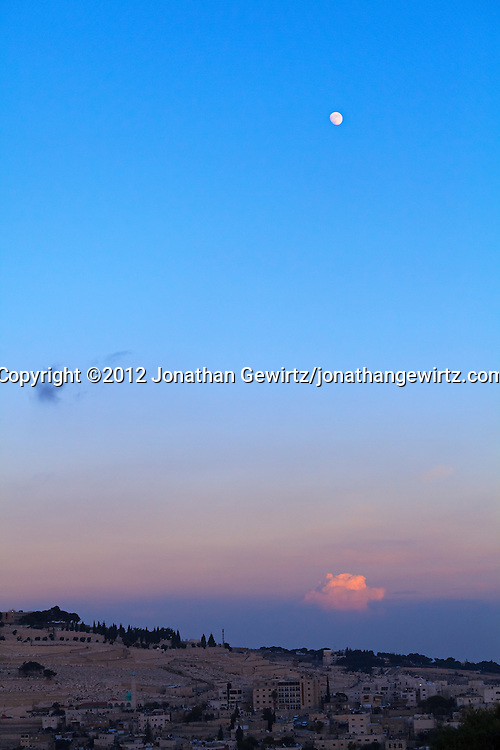 The Moon rises in the eastern sky at dusk over the southern edge of the Mount Zion cemetery and the Village of Silwan on the outskirts of Jerusalem. WATERMARKS WILL NOT APPEAR ON PRINTS OR LICENSED IMAGES.