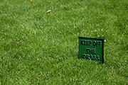 Green keep off the grass sign.