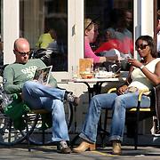Tjeerd Oosterhuis en vriendin Edsilia Rombley zittend op een terras in Amsterdam