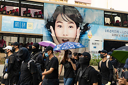 Hong Kong, China. 12th October 2019. Peaceful Pro-democracy march from tourist district of Tsim Sha Tsui along busy Nathan Road to Sham Shui Po Park in Kowloon. Some minor acts of vandalism to property were recorded but most marchers acted peacefully. Evening saw vigil at shrine at Prince Edward MTR  for protestor who died in police custody. Pic. Protestors march past bus with advertising on side. Iain Masterton/Alamy Live News.