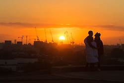 Primrose Hill, London, October 4th 2016. A couple watches the sunrise on Primrose Hill as dawn breaks across London, throwing the city's skyline into silhouette.