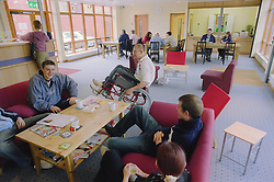 Group of young people; one a wheelchair user; sitting talking in reception of day centre for homeless and vulnerably housed young people,