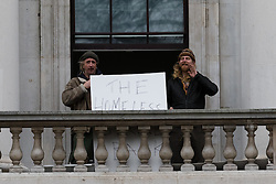 © Licensed to London News Pictures. 30/12/2015. London, UK. Two protesters on a balcony of the Royal Mint building. Squatters have occupied the former Royal Mint building, located opposite the Tower of London on the border of the City of London to protest against homelessness and highlight how empty buildings could provide shelter for rough sleepers. The site was previously used to manufacture British coins but is currently vacant and activists argue that this along with other vacant commercial buildings could be used to provide short term shelter for the homeless. Photo credit : Vickie Flores/LNP