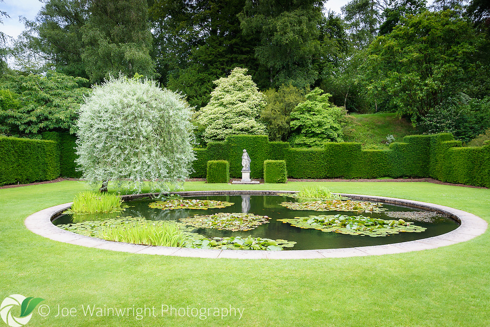 The pretty circular pond and statue in an enclosure of clipped yew, in the gardens of Knightshayes Court, Tiverton, Devon.