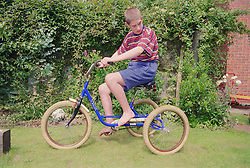 Teenage boy with autism riding tricycle in garden,