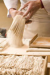 Asia, Japan, Gifu prefecture, Takayama (also known as Hida-Takayama), man slicing dough to make soba noodles
