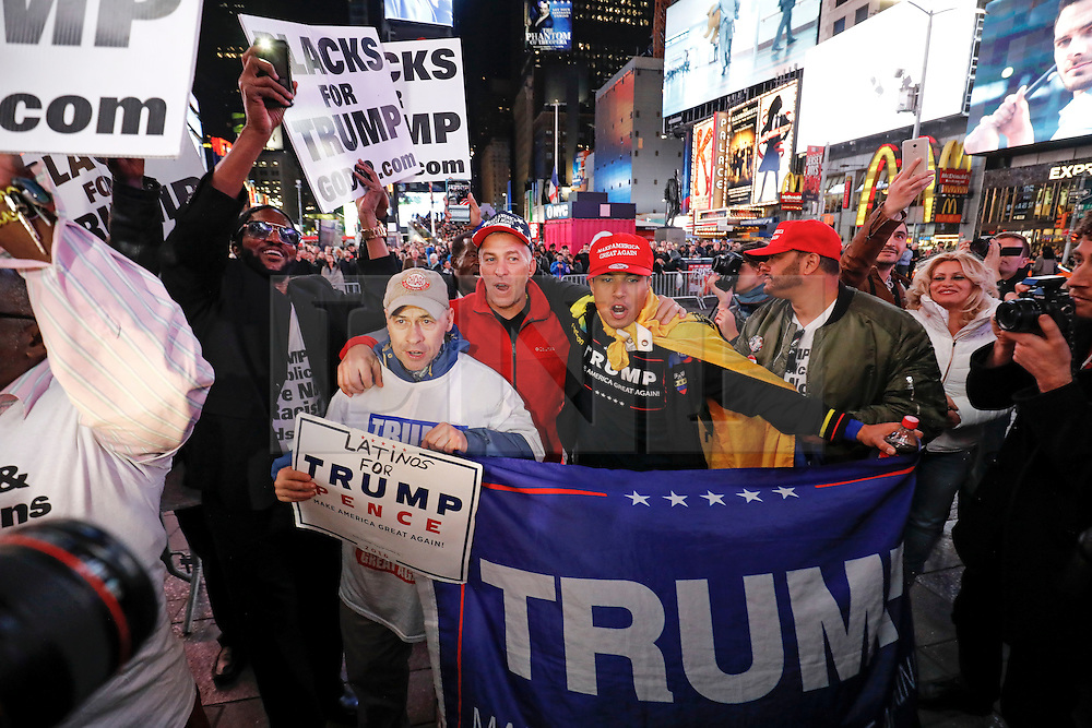 © Licensed to London News Pictures. 09/11/2016. New York City, USA. A group of Trump supporters react to news that Donald Trump looks likely to be elected as the next president of the United States, while gathering in Times Square, New York City, on Wednesday, 9 November. Photo credit: Tolga Akmen/LNP