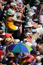 Spectators in the stands of court one shelter from the sun and apply sun lotion on day One of the Wimbledon Championships at the All England Lawn Tennis and Croquet Club, Wimbledon.