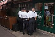Restaurant waiters share a joke on a smartphone in Naschmarkt, Vienna, Austria, EU.