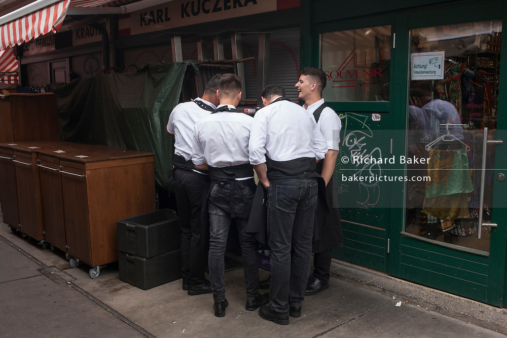 Restaurant waiters share a joke on a smartphone in Naschmarkt, Vienna, Austria, EU.