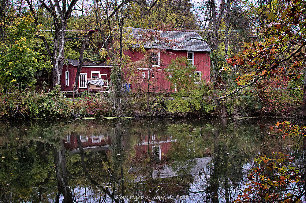 It is clearly autumn.  The leaves are changing and the canal is calm providing wonderful reflections of the barn, the sky and the different colored leaves.