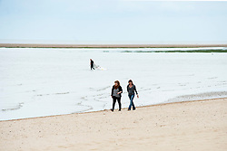 Walking on Cleethorpes beach. Cleethorpes is situated on Englands East Coast on the river Humber's tidal estuary. ..1 July 2012.Image © Paul David Drabble