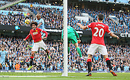 Vincent Kompany of Manchester City rises up against Marouane Fellaini of Manchester United to head the ball towards goal - Barclays Premier League - Manchester City vs Manchester Utd - Etihad Stadium - Manchester - England - 2nd November 2014  - Picture David Klein/Sportimage