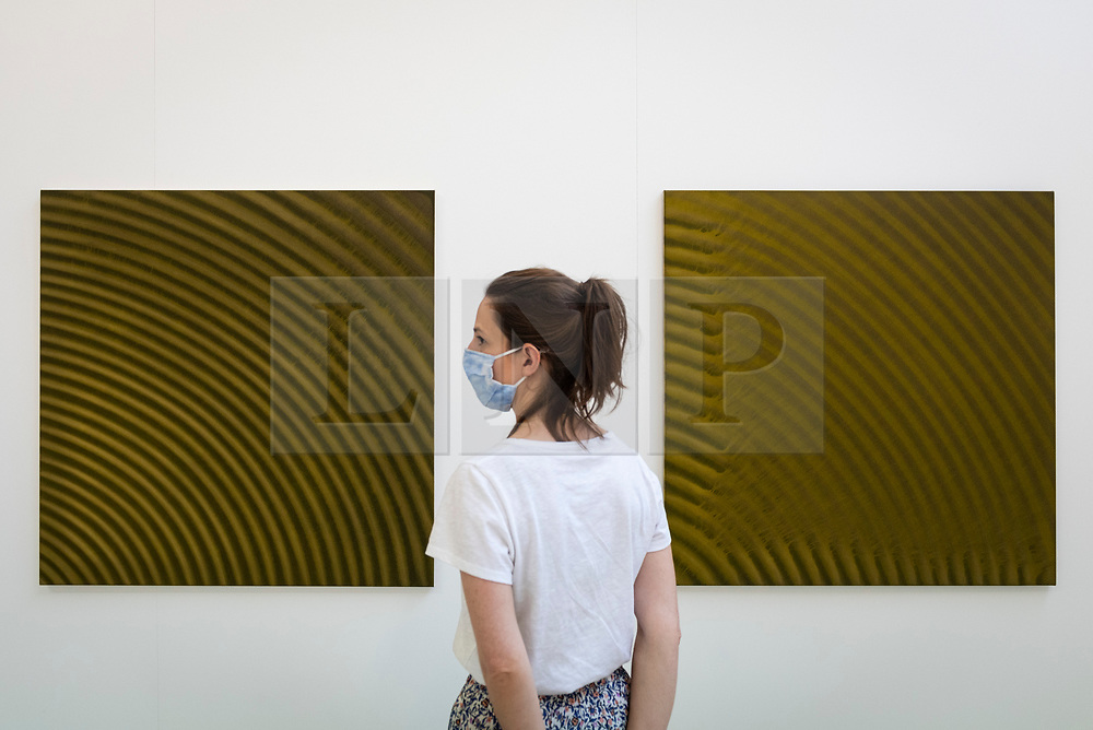 © Licensed to London News Pictures. 16/06/2021. LONDON, UK. A staff member poses with works by Paul Barlow at a preview of the RA Schools Show 2021, exhibiting the UK's newest artistic talent graduating from the RA Schools at the Royal Academy of Arts until 4 July 2021.  Photo credit: Stephen Chung/LNP