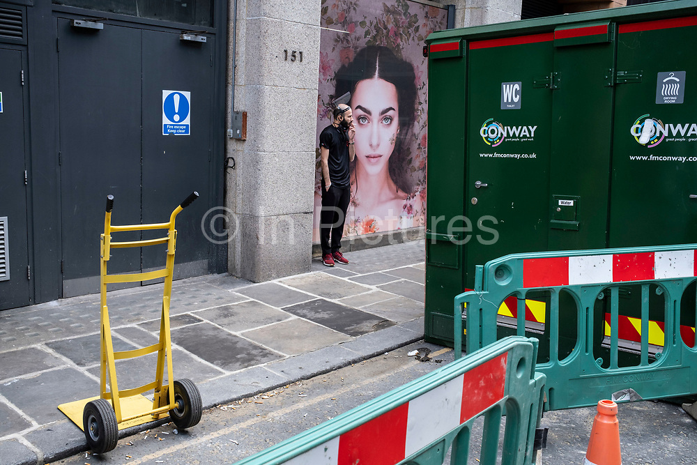Face of a beautiful model outside a beauty salon peering from behind various barriers from nearby works, blocking the road in the upmarket area of Chelsea on 14th April 2021 in London, United Kingdom. Chelsea is one of the principal areas for exclusive, luxury goods in West London. It is known as a district where the rich and wealthy shop, mostly for high end fashion and jewellery.