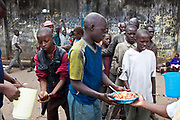 At Mbaraki base in central Mombassa the Wema centre provide a hot meal once a week to the street children. Most of them are male aged between 7 and 30 years old. Most of them sniff glue, hidden in bottles down their t-shirts. Staff from the Wema centre wash their hands and hand out bowls of rice and beans.  Wema is an NGO in Kenya supporting vulnerable children.