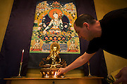 The Buddhist monk Nagasiddhi lights candles in the Shrine Room at the Rivendell Buddhist Retreat Centre, East Sussex, England.