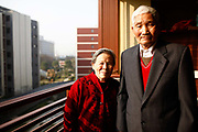 An elderly couple stands on the balcony of their apartment at the Cherish-Yearn retirement community on the outskirts of Shanghai, China, on Tuesday, Dec. 13, 2011. China has about  36000 institutions and 2.7 million beds serving the elderly, enough for 1.6 percent of the population over 60, according to the World Bank.