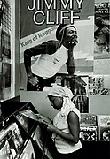Girl selecting a record, beneath Jimmy Cliff poster, in record shop. Photo by Richard Saunders 1983