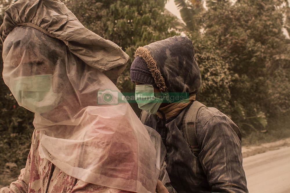 August 3, 2017 - Karo, North Sumatra, Indonesia - Locals resident cover their faces with plastic bags when the eruption of Sinabung erupts pyroclastic flows into the air, in Karo on August 2, 2017, Indonesia. The volcano destroys volcanic ash as high as 4.2 kilometers (2.2 miles), one of its biggest eruptions. In recent months high activity. (Credit Image: © Ivan Damanik via ZUMA Wire)