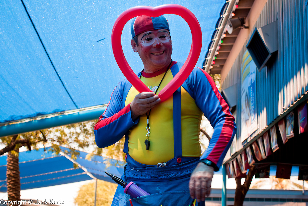 """July 25 - PHOENIX, AZ: Oliver El Payaso (The Clown) makes balloons animals for kids in El Gran Mercado. Oliver said he's been a clown in the market for more than 16 years and that, """"this used to be a good business. Now, nothing. Everyone is gone."""" El Gran Mercado (The Big Market) in Phoenix is the largest flea market in the Phoenix area and has served the area's immigrant community for more than 20 years. With more than 150 small independent stalls selling Mexican clothes, cowboy hats, Mariachi music and food stalls selling Mexican favorites like birria chivo (goat stew) and menudo (tripe) it was more like a Mexican market than an American mall. Business in the mercado is down more than half this year because many immigrant families, legal and illegal, are leaving Arizona before the state's tough new anti-immigrant law, SB 1070 goes into effect on July 29. SB 1070 allows local police officers to check the immigration status of people they have probable cause to believe may be in the US illegally and requires immigrants to carry their immigration papers with them at all times.    Photo by Jack Kurtz"""
