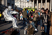 An entertainer dressed in a silver suit and a funny nose pretend to be floating in the air.  A large number of performers earn their money outside the national Gallery and the trade is good on a sunny day.