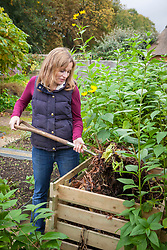 Turning over the compost heap with a fork to speed up the process of decomposition