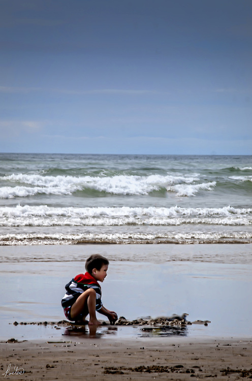 Young boy playing in the sand at the beach.