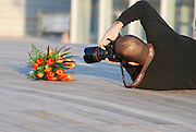 Wedding photographer at work laying on the ground with a flower bouquet in the forground