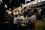 Childen have lunch  amidst the squalor of their slumb which lies under a Rio de Janeiro city overpass close to the world famous Maracana football stadium, Brazil