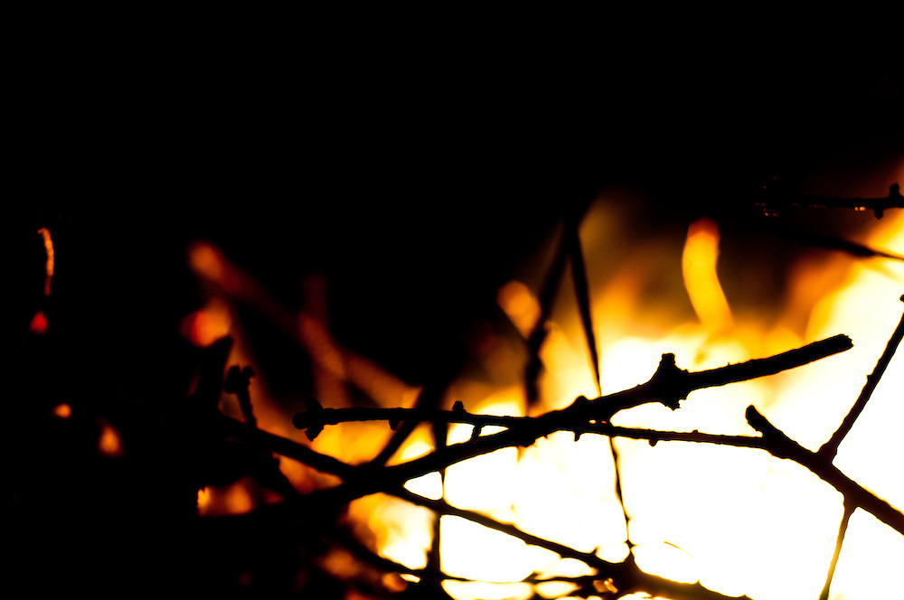 The flame of a burning Christmas tree mingles with darkness at Golden Gardens park, Seattle, Washington. This is a annual tradition with my friends.