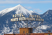The historic Hotel Monte Vista sign in downtown Flagstaff Arizona with the snow capped San Francisco Peaks in the background.