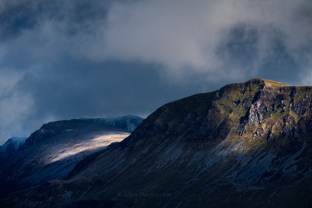 Fleeting patches of light caress the slopes of the ancient mountain of Cader Idris during squally winter weather. Clouds build and billow at speed above the peaks, in contrast to the dark shadows of the huge North facing cliffs.