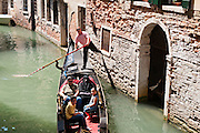 """Gondolas are traditional, flat-bottomed rowing boats which ferry people through Venetian canals. From a peak of 10,000 gondolas 200 years ago, just 500 gondolas now serve Venice. The banana-shaped modern gondola was developed in the 1800s. The left side of the gondola is made longer than the right side to resist leftwards drift at the forward stroke. The gondolier stands on the stern facing the bow and rows just on the right side, with a forward stroke and compensating backward stroke. The oar or rèmo is held in an oar lock, or fórcola, shaped for several rowing positions. The decorative fèrro (meaning iron) ornament on the front can be made of brass, stainless steel, or aluminum, as counterweight for the gondolier standing near the stern. The six horizontal lines and curved top of the ferro represent Venice's six sestieri (districts) and the Doge's cap. Painting gondolas black originated as a sumptuary law banning ostentatious competition between nobles. Until the early 1900s, many gondolas had a small cabin (felze) with windows which could be closed with louvered shutters--the original """"venetian blinds."""" The romantic """"City of Canals"""" stretches across 117 small islands in the marshy Venetian Lagoon along the Adriatic Sea in northeast Italy, Europe. Venice and the Venetian Lagoons are honored on UNESCO's World Heritage List. For licensing options, please inquire."""