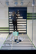 A window dresser prepares a new window design with a stripes theme in the Oxford Street branch of retailer Debenhams. We see from the rear, a lady retail professional who is standing on a square box in order to reach the upper corners of the background - formerly stripy and when she's finished, a solid black. Debenhams plc is a British multinational retailer operating under a department store format in the United Kingdom and Ireland with franchise stores in other countries