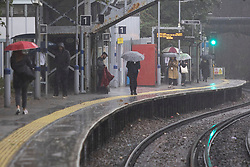 © Licensed to London News Pictures. 14/09/2021. London, UK. Commuters shelter under umbrellas during heavy rain at Maze Hill station in Greenwich . A yellow weather warning for rain is in place in parts of England . Photo credit: George Cracknell Wright/LNP