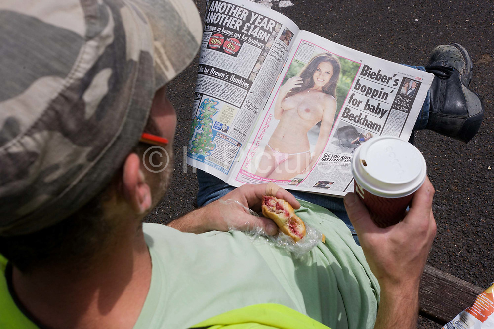 """A labourer reads a copy of Britain's tabloid Sun Newspaper. The worker holds a coffee and wears a working mans' cap with a pencil in his right ear as he sits in sunshine during a lunch break. Page Three (or Page 3) is a tabloid newspaper photograph consisting of a topless female glamour model, usually printed on the paper's third page. Women who model regularly for the feature are known as Page Three girls. """"Page Three"""" and """"Page 3"""" are registered trademarks of the Sun tabloid, where the feature originated in 1970. In the context of the News International media scandals of 2011, the (daily) Sun is a sister paper to the now defunct (Sunday) News of The World, closed down by proprietor Rupert Murdoch in the light of public outrage over phone hacking."""