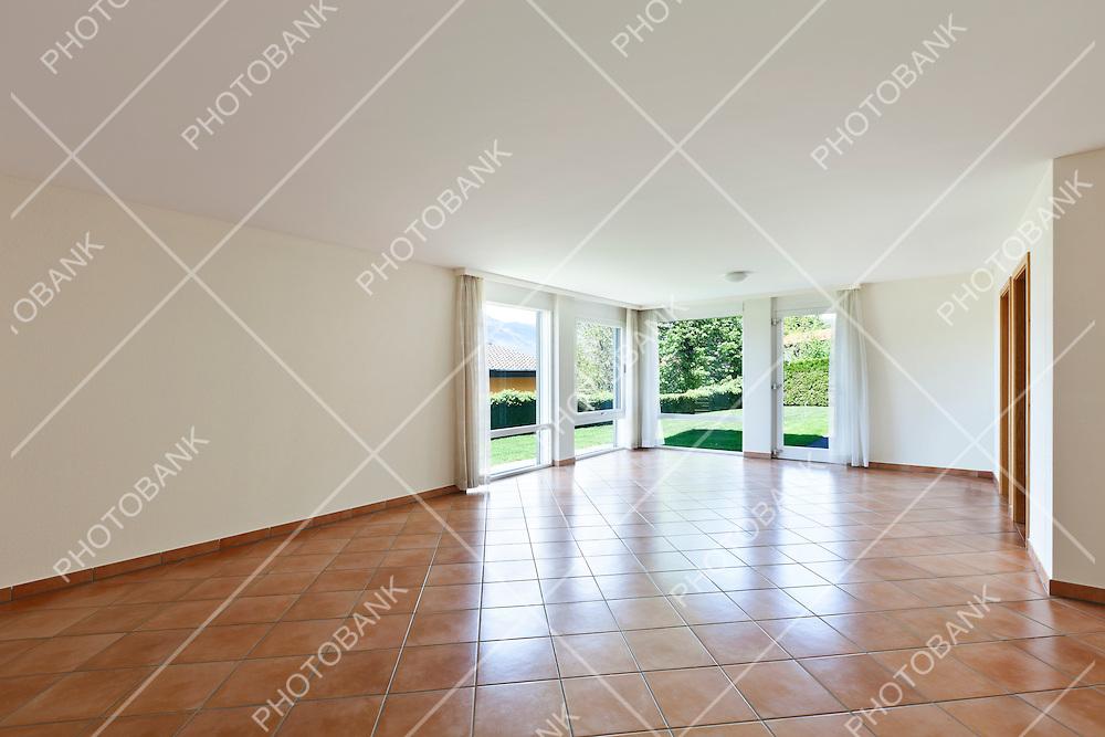 room with terracotta floor, windows overlooking the garden