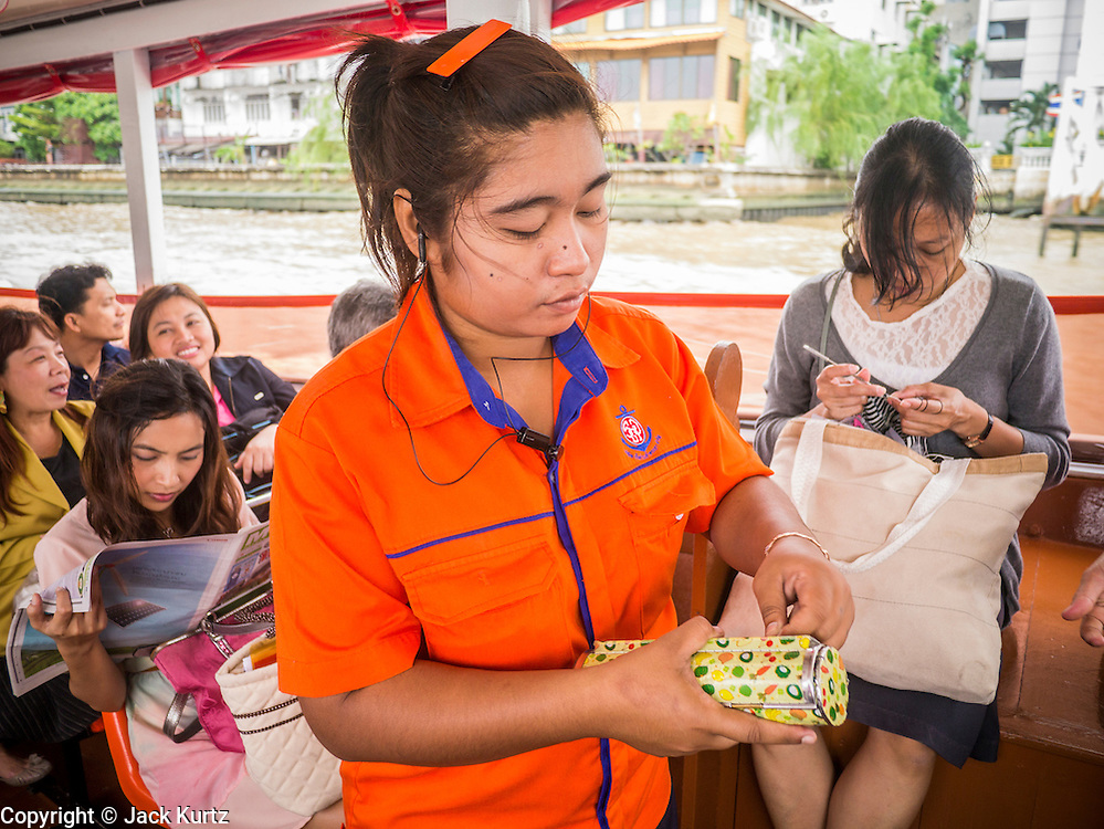 09 OCTOBER 2012 - BANGKOK, THAILAND:  A ticket taker collects fares on a Chao Phraya Express boat on the Chao Phraya river in Bangkok, Thailand. Boats and ships play an important in daily life in Bangkok. Thousands of people commute to work daily on the Chao Phraya Express Boats and fast boats that ply Khlong Saen Saeb. Boats are used to haul commodities through the city to deep water ports for export.       PHOTO BY JACK KURTZ