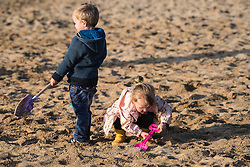 Two children playing in the sand on Fistral Beach in Newquay, Cornwall. Model released