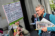 "Environmental protest at the Drax AGM, the Grocer's Hall, London 22 Apr 2015. London Rising Tide and Biofuelwatch attempt to expose and oppose burning biomass and coal. They claim that Drax Power Station has ""led the way for the industry: lobbying; greenwashing; converting and building the necessary infrastructure; and clearcutting hugely biodiverse native forests in the southern US and Canada"". They also believe that 'Drax exemplifies much that is wrong with UK energy policy and ""renewable"" energy subsidies'.  Guy Bell, 07771 786236, guy@gbphotos.com"