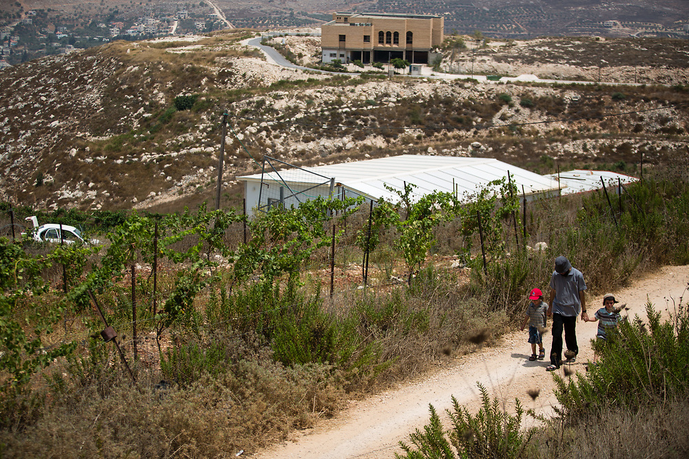 A Jewish Israeli settler and his children walk up an unpaved road in the West Bank Jewish settlement of Yitzhar, south of the Palestinian West Bank city of Nablus, on August 5, 2015.